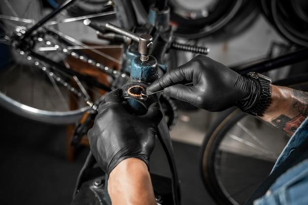 Mann in der werkstatt, die fahrrad schafft