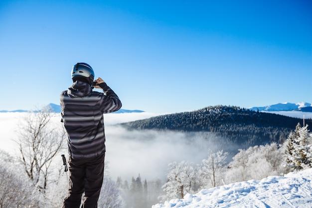 Mann in der winterkleidung, die ein selfie mit bergen nimmt
