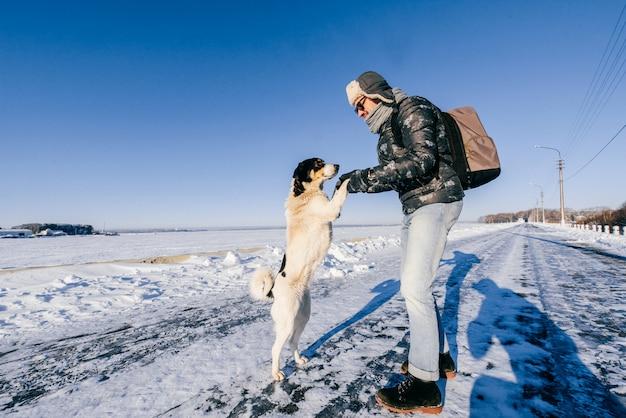 Mann in der winterkleidung, die um obdachlosem hund sich kümmert.