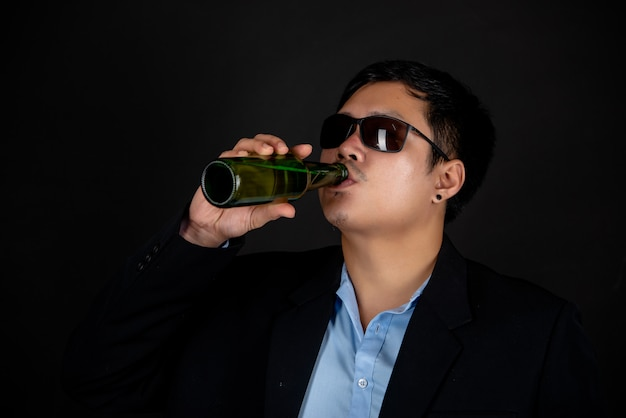 Mann in dunkler jacke und sonnenbrille trinkt eine bierflasche
