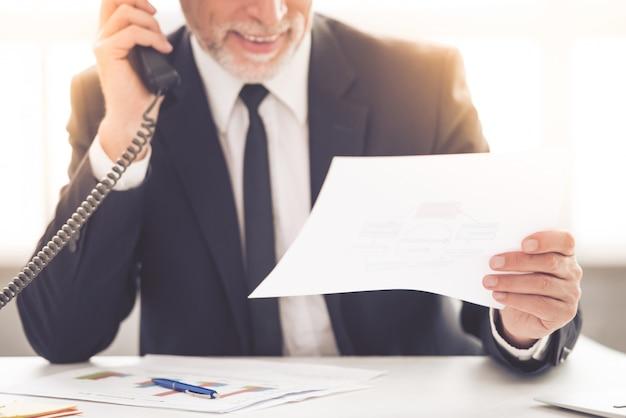 Mann in einem anzug, der ein papierdokument betrachtet