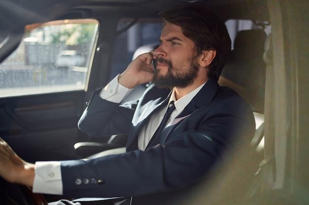 Mann in einem anzug, der einen autoerfolgsbeamten fährt, der am telefon spricht