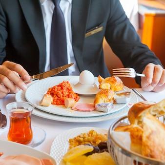 Mann in einem anzug, der frühstück in einer küchenseitenansicht hat