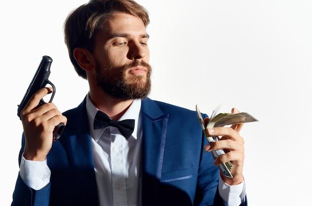 Mann in einem anzug mit einer pistole in der hand isolierter hintergrund