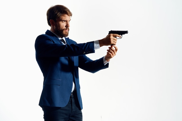 Mann in einem anzug mit einer waffe in den händen detektiv verbrechen vorsicht