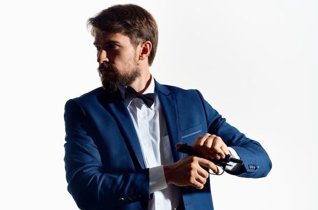 Mann in einem anzug mit einer waffe in der hand heller hintergrund