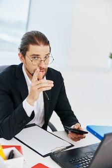Mann in einem anzug telefon laptop arbeiten emotionen technologien. foto in hoher qualität