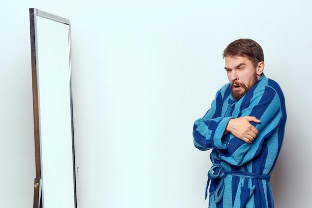 Mann in einem blauen gewand untersucht sich in einem spiegel