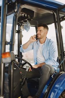 Mann in einem blauen hemd. kerl in einem traktor. landwirtschaftliche maschinen.