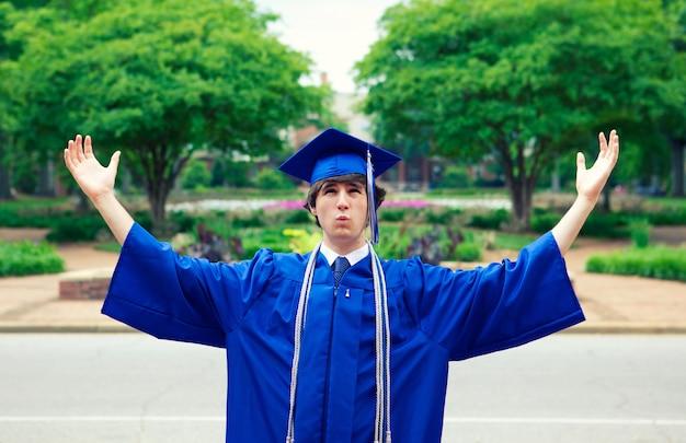 Mann in einem blauen mantel, der die freiheit nach abschluss genießt