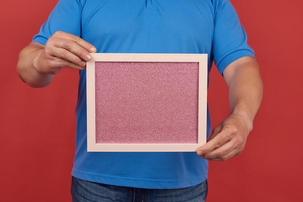Mann in einem blauen t-shirt hält einen leeren rechteckigen rosa rahmen zum schreiben von text, roter hintergrund
