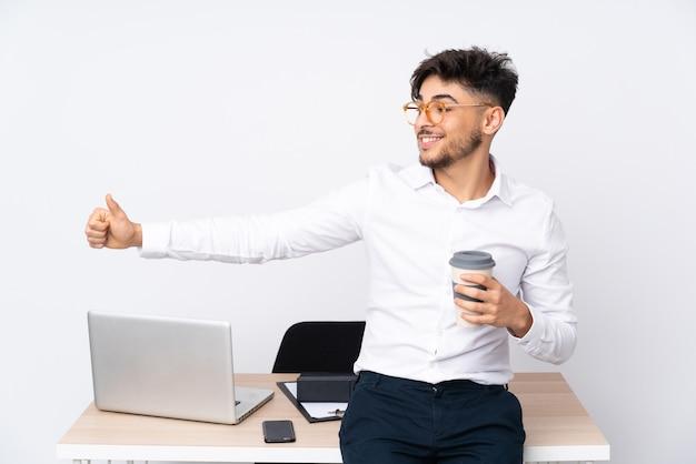Mann in einem büro, das auf weiß isoliert ist und eine daumen hoch geste gibt