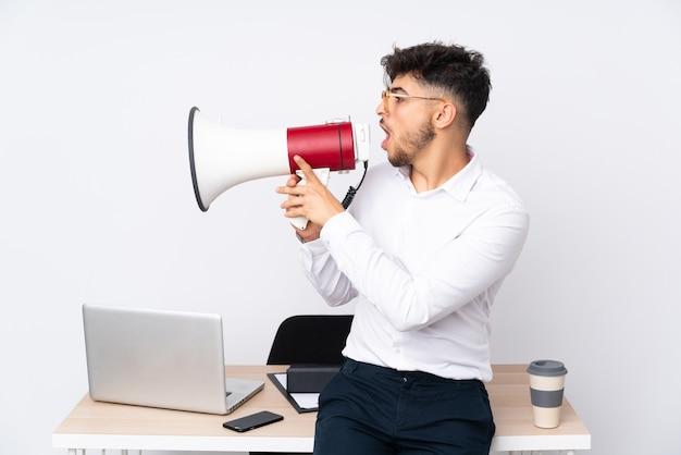 Mann in einem büro isoliert auf weiß, das durch ein megaphon schreit