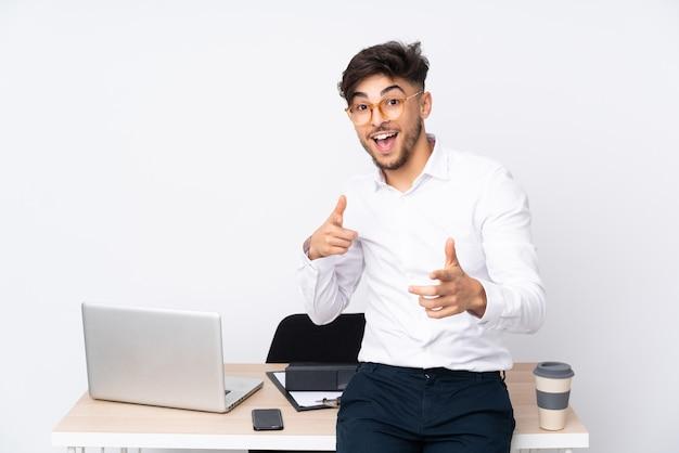 Mann in einem büro lokalisiert auf weißer wand, die nach vorne zeigt und lächelt
