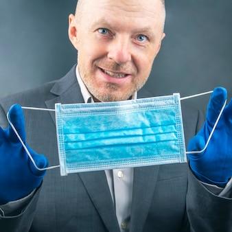Mann in einem business-anzug schlägt vor, während einer coronavirus-epidemie eine medizinische schutzmaske in quarantäne zu verwenden.