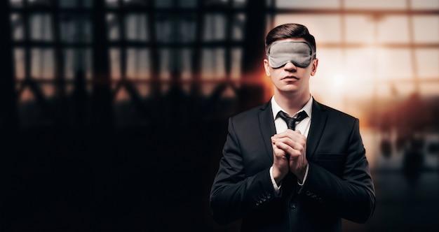 Mann in einem geschäftsanzug und einer maske zum schlafen steht am flughafen