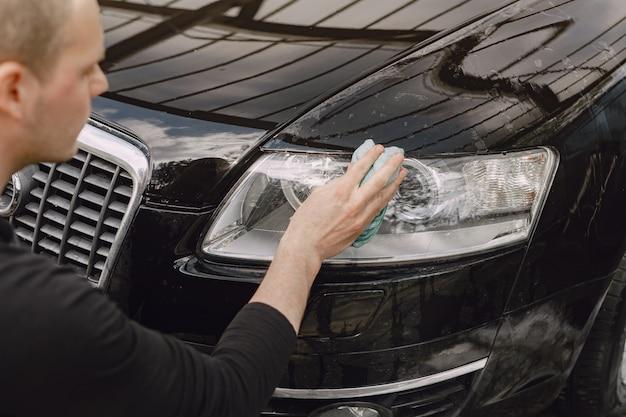 Mann in einem grauen pullover wischt ein auto in einer autowäsche ab