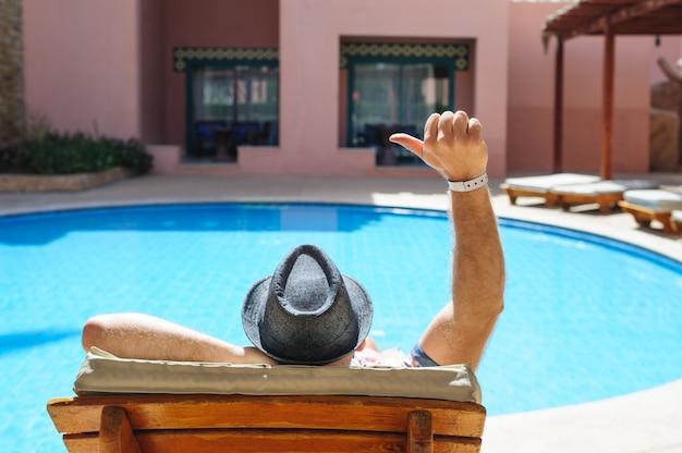 Mann in einem hut, der auf einer liege am pool liegt, und zeigt handzeichen ok