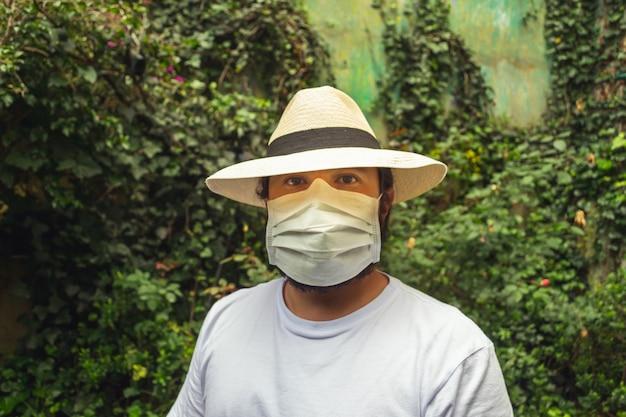 Mann in einem hut, der eine weiße gesichtsmaske trägt, um vor staub und coronavirus im garten zu schützen
