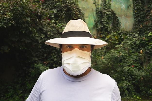 Mann in einem hut, der eine weiße gesichtsmaske trägt, um vor staub und coronavirus zu schützen