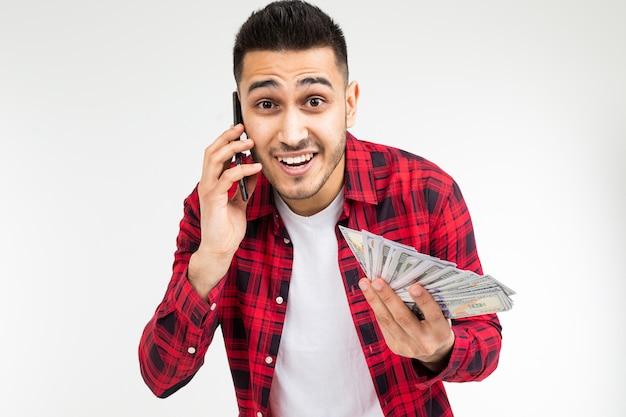 Mann in einem karierten hemd berichtet, geld per telefon auf einem weiß mit kopierraum zu gewinnen