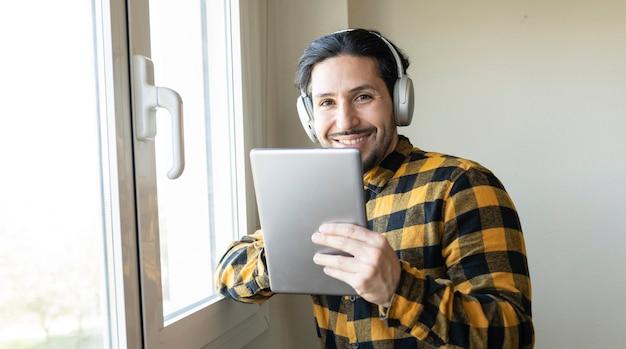 Mann in einem karierten hemd, der sich mit einem tablet in der hand an ein fenster lehnt, musik hört und in die kamera schaut