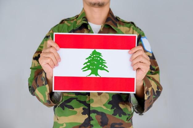 Mann in einem militärhemd, das die flagge des libanon hält.
