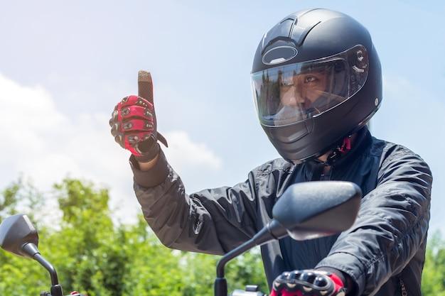 Mann in einem motorrad mit sturzhelm und handschuhen ist schutzkleidung für das motorradfahren