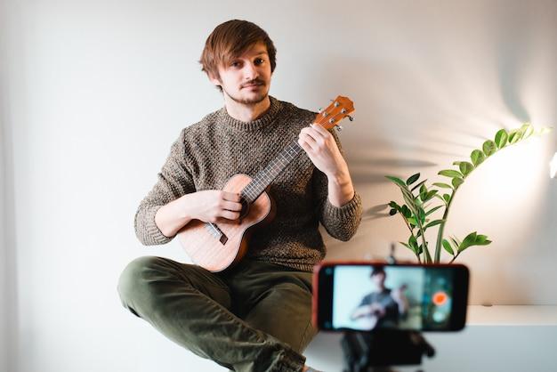 Mann in einem pullover zieht den vlog eines spiels auf einer ukulele zu hause am telefon aus.