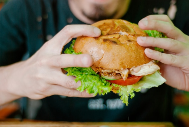 Mann in einem restaurant einen hamburger essend
