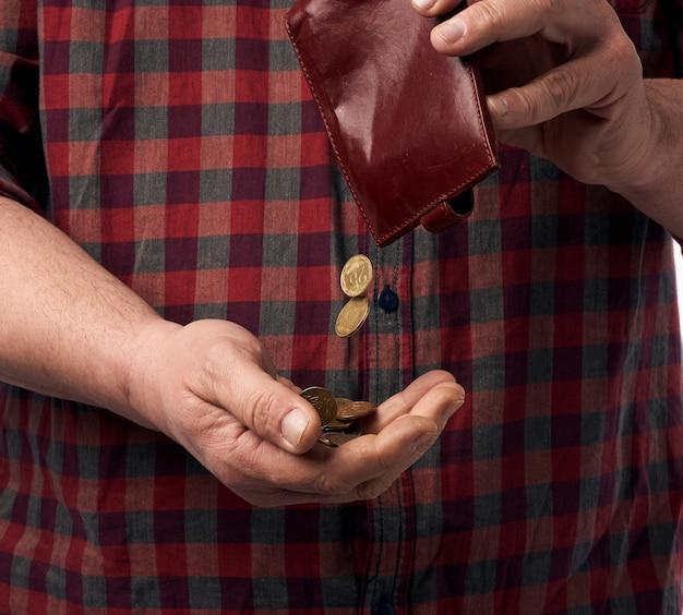 Mann in einem roten hemd gießt griwna-münzen aus einer braunen lederbrieftasche in seine hand