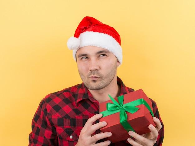 Mann in einem roten hut, der ein weihnachtsgeschenk hält