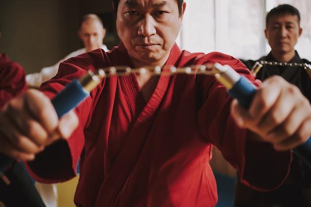Mann in einem roten kimono, der ein nunchuck in seinen händen hält.