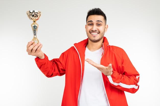 Mann in einem roten trainingsanzug zeigt den goldpokal des gewinners