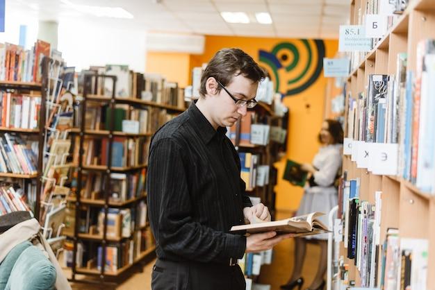 Mann in einem schwarzen hemd, das ein buch in der bibliothek wählt