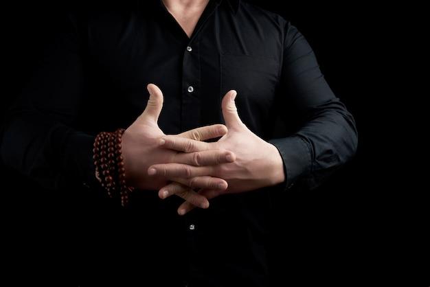 Mann in einem schwarzen hemd kreuzte seine finger