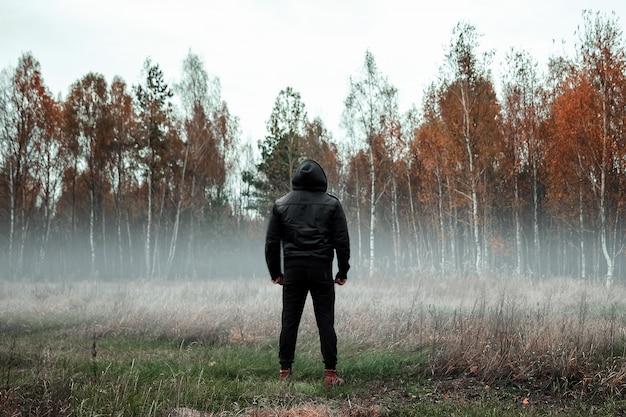 Mann in einem schwarzen mantel bei nebel