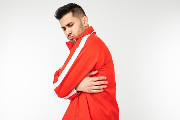 Mann in einem sportroten anzug umarmt sich, um sich auf einem weißen hintergrund mit kopierraum warm zu halten