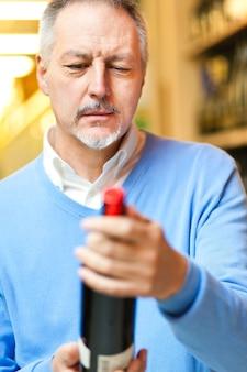 Mann in einem supermarkt, der eine weinflasche wählt