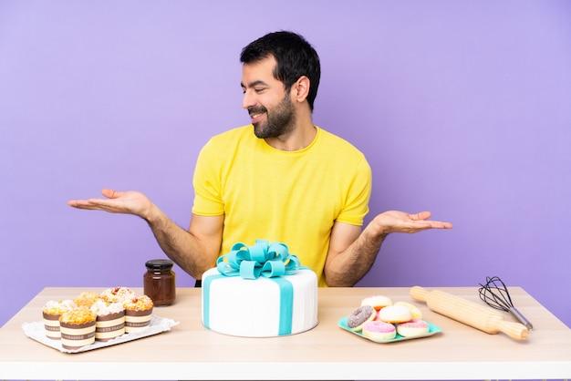 Mann in einem tisch mit einem großen kuchen, der copyspace mit zwei händen hält