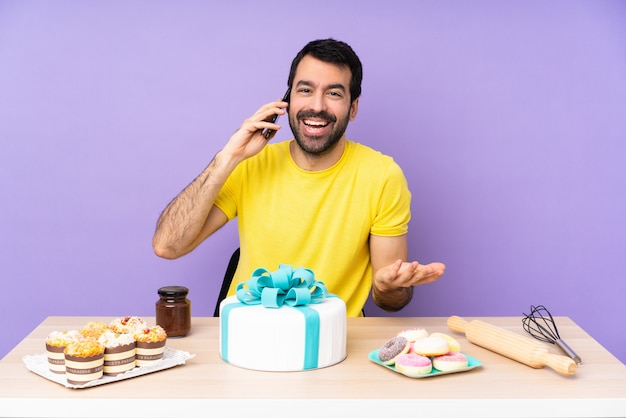 Mann in einem tisch mit einem großen kuchen, der ein gespräch mit dem handy mit jemandem führt