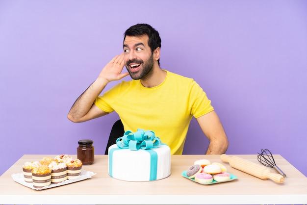 Mann in einem tisch mit einem großen kuchen, der etwas hört, indem er hand auf das ohr legt