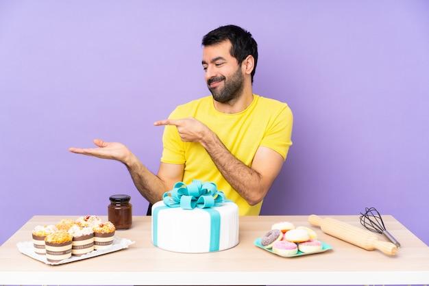 Mann in einem tisch mit einem großen kuchen, der imaginären copyspace auf der handfläche hält, um eine anzeige einzufügen