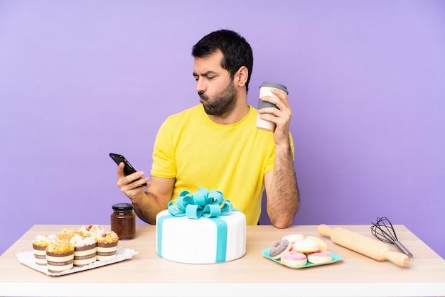 Mann in einem tisch mit einem großen kuchen, der kaffee zum mitnehmen und ein handy hält