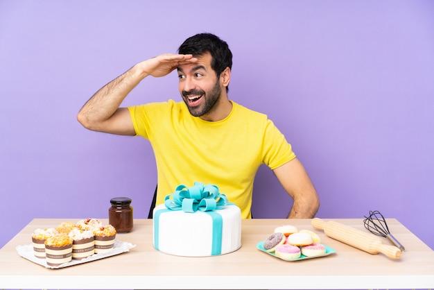 Mann in einem tisch mit einem großen kuchen, der weit weg mit der hand schaut, um etwas zu schauen
