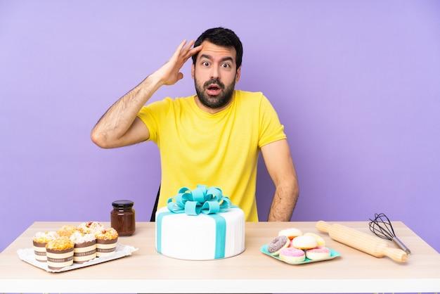 Mann in einem tisch mit einem großen kuchen hat gerade etwas realisiert und die lösung beabsichtigt