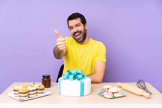 Mann in einem tisch mit einem großen kuchen mit daumen hoch, weil etwas gutes passiert ist