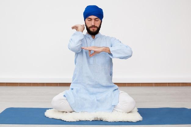 Mann in einem turban sitzt auf der matte und macht mudra