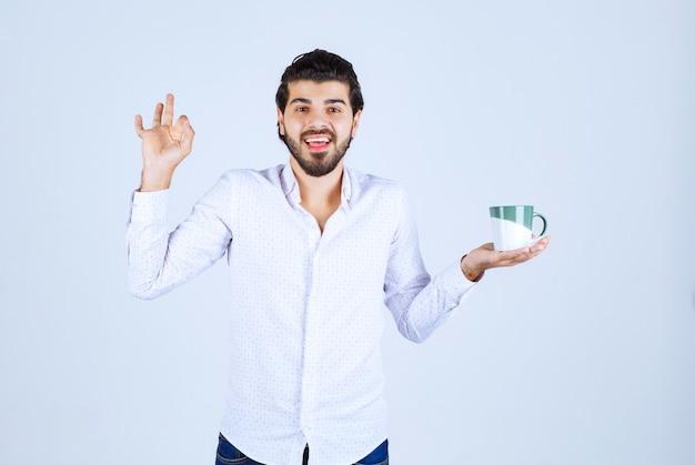 Mann in einem weißen hemd, das eine kaffeetasse hält und sie genießt.