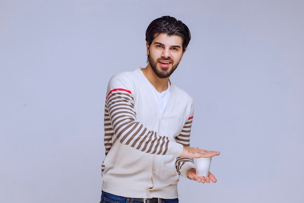 Mann in einem weißen hemd, das eine kaffeetasse hält.